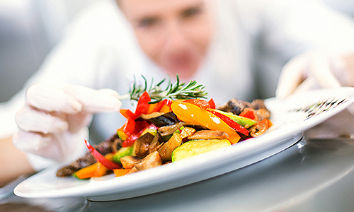 A chef putting the finishing touches on a plate of stir fry