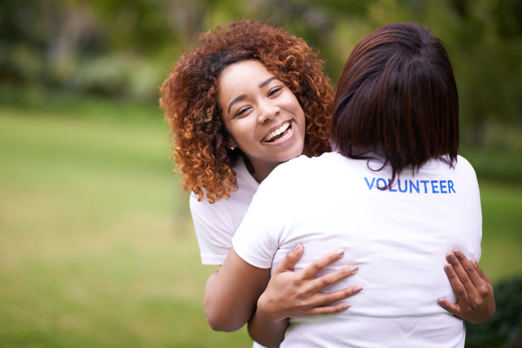 Two volunteers hugging each other and laughing