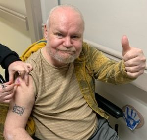 Long-term care resident smiles and gives a thumbs up as he receives his COVID-19 vaccine