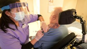 Nurse gives a long-term care resident in a wheelchair his COVID-19 vaccine