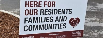 Lawn sign that says here for our residents families and communities
