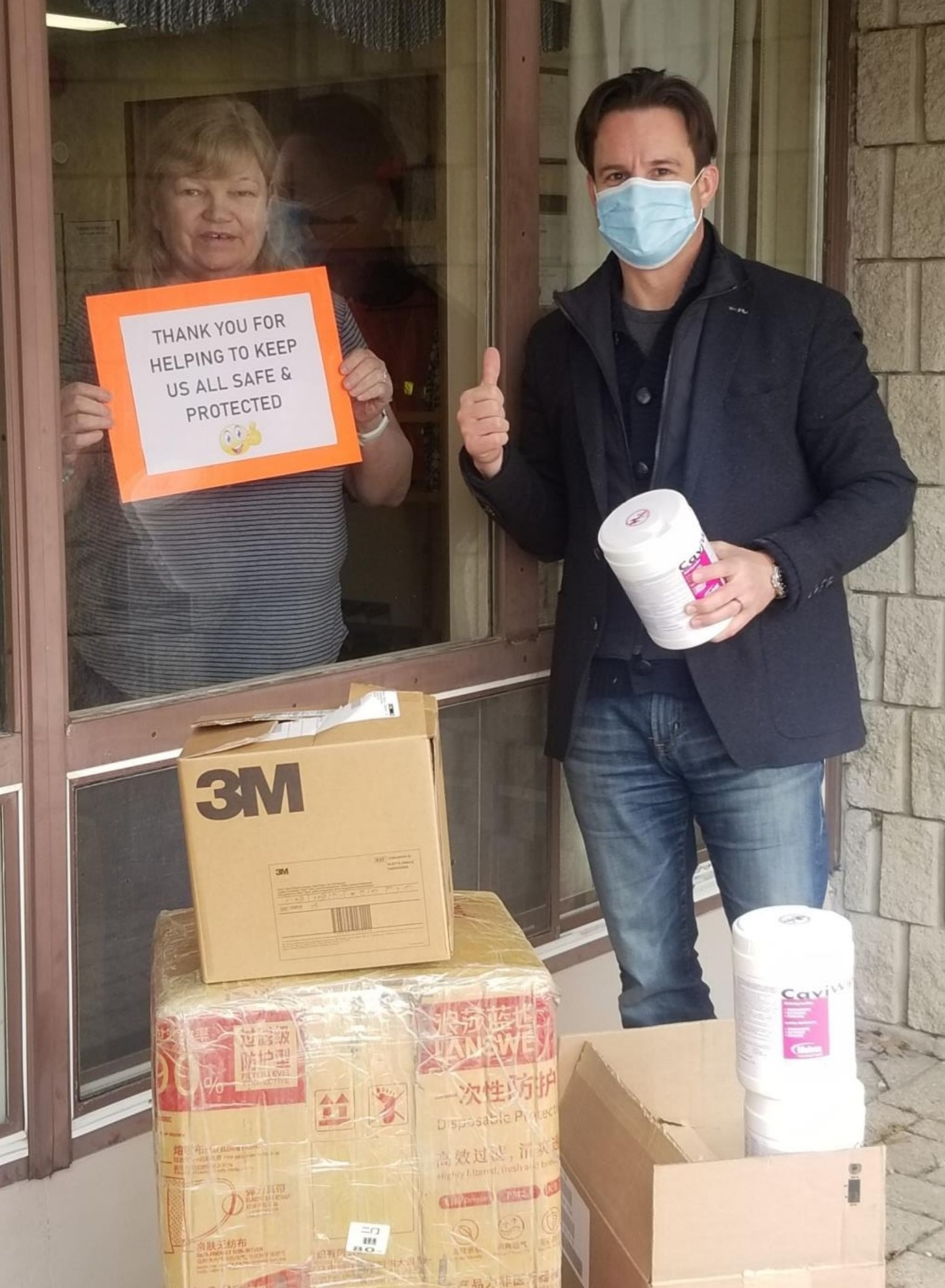 peopleCare CEO drops off PPE and supplies to long-term care home while a resident stands next to the window with a sign