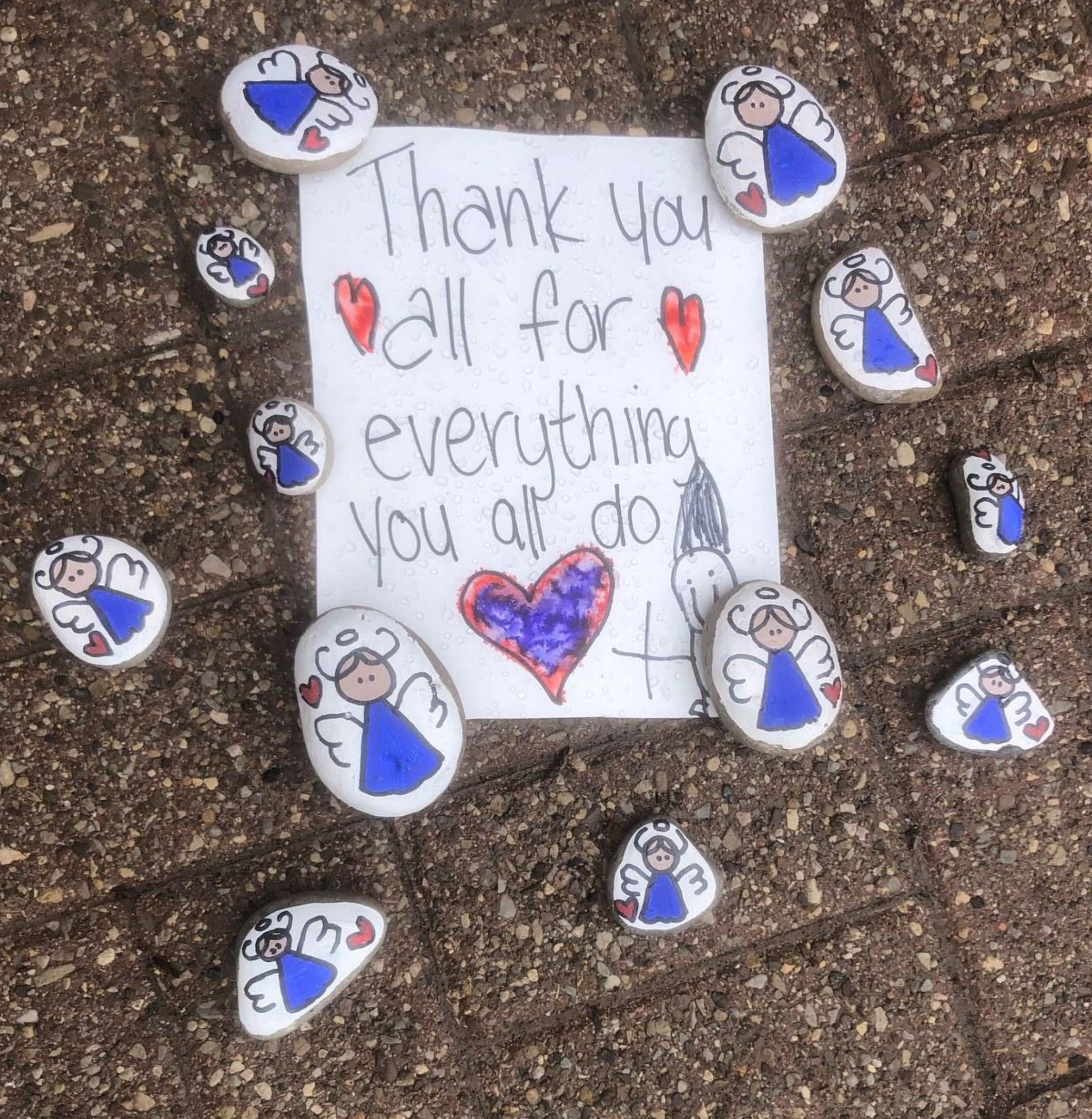 A hand written thank you note and painted rocks placed on the ground outside a long term care home