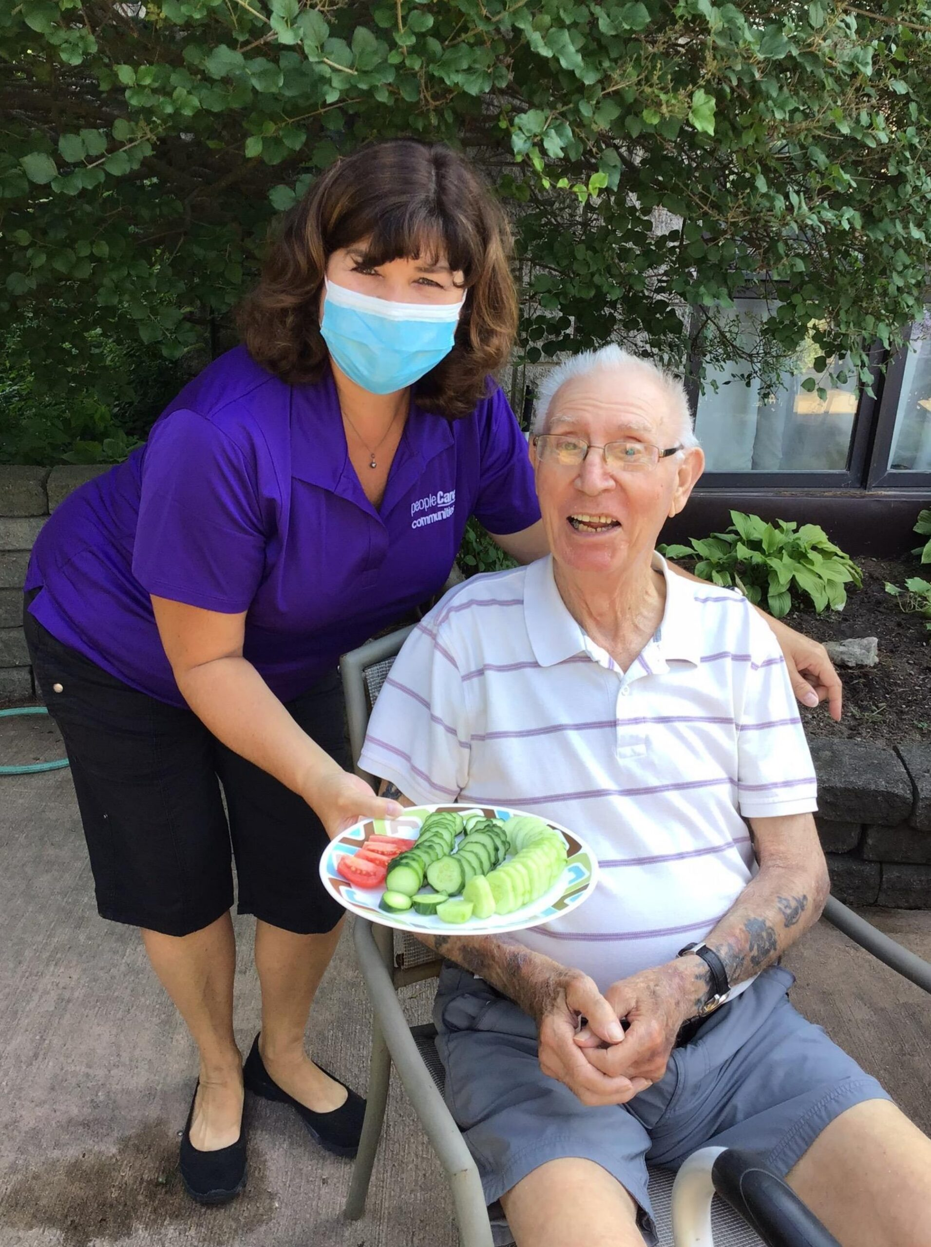 Staff member holding vegetables from the garden while standing next to a resident from a long-term care home