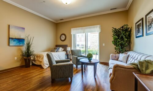 Bed and seating area in studio suite at Oakcrossing Retirement Living