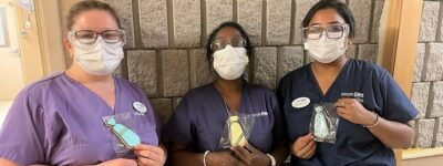 three peopleCare staff members holding cookies